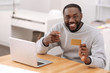 Handsome delighted man pointing at the credit card