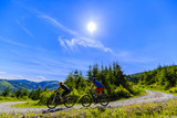 Mountain biking women and man riding on bikes in summer mountains forest landscape. Couple cycling outdoor sport activity.