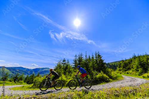 Mountain biking women and man riding on bikes in summer mountains forest landscape Poster