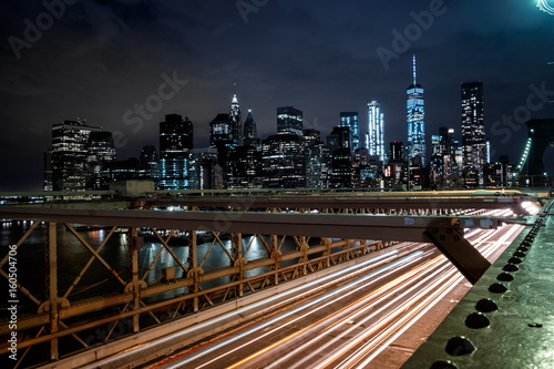 View from the Brooklyn Bridge at night with the One World Trade Center and traff плакат