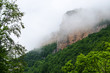 Haze fog over the rocks. Cloud over the mountainin Caucasus. Green leaf forest. Mezmay and Guamka