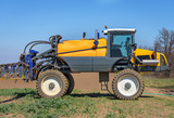 Farm machinery spraying insecticide to the green field.
