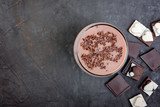 Chocolate smoothie (milkshake) with banana and chocolate pieces on a dark table.