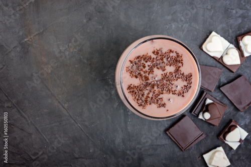 Foto op Aluminium Milkshake Chocolate smoothie (milkshake) with banana and chocolate pieces on a dark table.