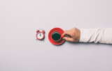 Man holding red cup of coffee near alarm clock