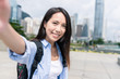Woman taking selfie with mobile phone in Hong Kong