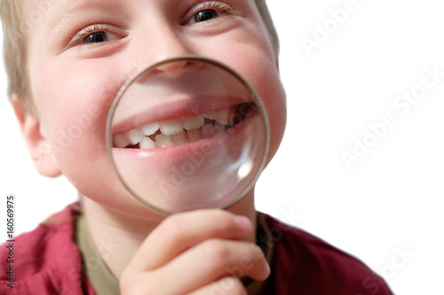 kid showing his smile with teeth through loupe, isolated