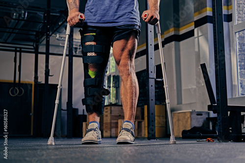 Injured bodybuilder's leg in bandage with crutches. - 160581327