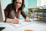 Beautiful architect at her working desk with blueprints in front of her. Working on new projects. Architecture and design