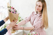 Delivery of a floral workshop. The customer receives his order-a bouquet of pink tulip. Hand florist pass flowers to the buyer