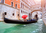 Woman with a red umbrella in Gondola passing over Bridge of Sighs in Venice