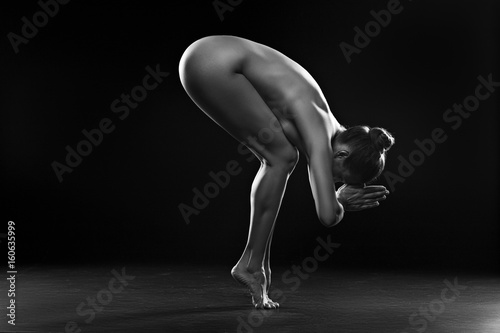 Nude woman making exercise for relaxation