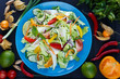 Fresh vegetable thai salad with soybean sprouts on blue plate, decorated with physalis, chili peppers, lime, herbs and spices