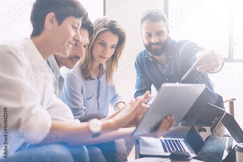Concept of presentation new business project.Group of young coworkers discussing ideas with each other in modern office.Business people using electronic devices.Horizontal, blurred background.