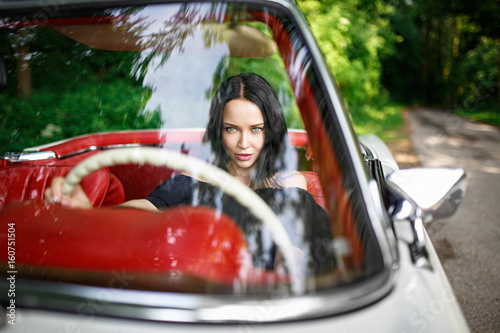 Beautiful girl in a black hat driving vintage car