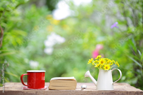 Coffee in red cup and notebook on wooden table
