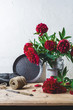 Bouquet of red peonies in a can on a wooden table against the background of a white wall