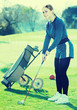 Young woman playing golf is going to hit ball