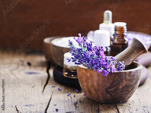 Papiers peints Lavande Lavender spa , bunch of lavender flowers , essential oil and salt on a rustic wooden background.