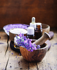 Lavender spa , bunch of lavender flowers , essential oil and salt on a rustic wooden background.