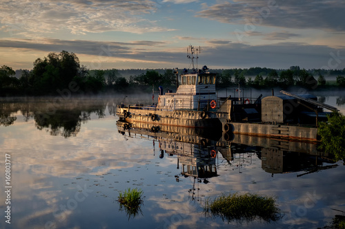 Tugboat on a river in the early morning on a misty river © chizh_marina
