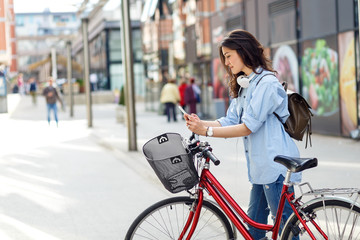 Beautiful young woman with bicycle in urban environment.