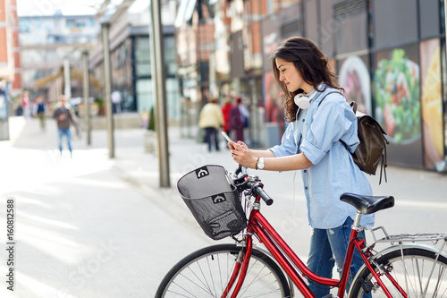 Beautiful young woman with bicycle in urban environment. - 160812588