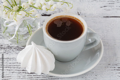 Background cup of espresso coffee spring lily of the valley bouquet