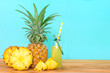 Quadro The Bottles of pineapple juice with sliced pineapple fruit on wooden table with fresh blue background , summer fruit drink concept