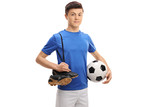 Teenage soccer player with football and pair of soccer shoes
