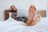 Smiling man lying in bed with laptop