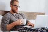 Handsome bearded man working with laptop in bed