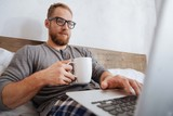 Cheerful man drinking coffee and working with laptop in bed