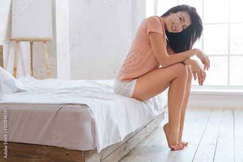 Smiling brunette sitting on bed Poster