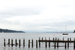 Gulls on wooden pier on Lake Starnberg , Germany with bright clear blue sky and mountains background.