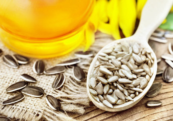 Spoon of dehulled kernels on sunflower seeds and oil background