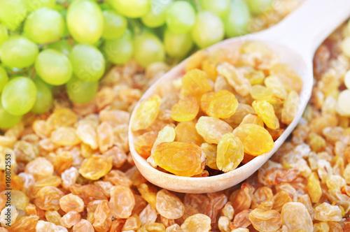 Spoon of dried yellow raisins with fresh organic grapes