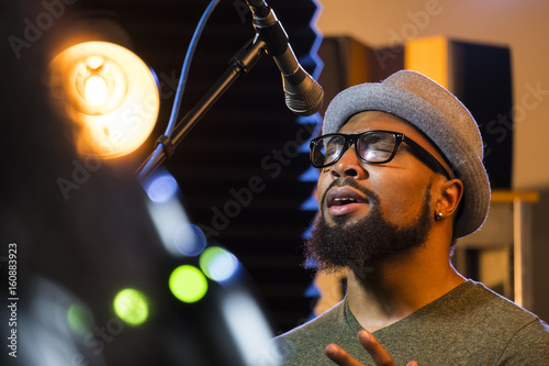 Black male singing in a recording studio, close up