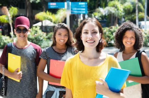 Lachende deutsche Studentin mit anderen Stundenden in der Stadt Poster