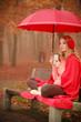 Quadro Girl in autumn park enjoying hot drink