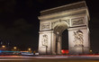View of Arc de Triomphe at night. Light trails of cars in motion are also in the view.