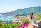 Back view of young woman background stunning town. Tourist looking at scenic view of Cinque Terre, Liguria, Italy