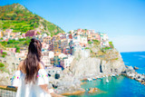 Back view of young woman background stunning village. Tourist looking at scenic view of Manarola, Cinque Terre, Liguria, Italy