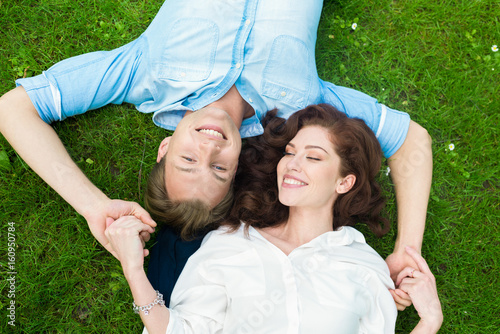 Couple in love lying down on the grass Poster