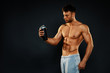 Attractive fitness man holding a bottle with protein shake