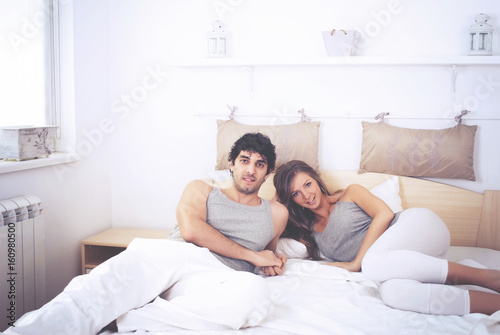 Couple laughing in bed and they are happy Poster
