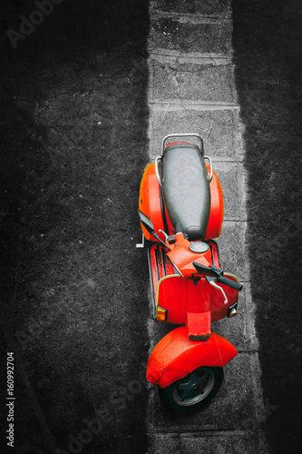 Staande foto Scooter Red vintage scooter on a black and white background