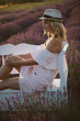 Quadro Young beautiful woman enjoy nature. Blonde hair woman relaxing on bench in a lavender field and enjoy sunset.