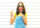 Fototapety Fashion cool girl eating a slice of watermelon in the form of ice cream on a white background
