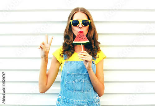 Leinwanddruck Bild Fashion cool girl eating a slice of watermelon in the form of ice cream on a white background